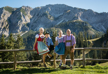 Young Bavarian Family In A Beautiful Mountain Landscape. Happy Parent And Smiling Children In Traditional Bavarian Clothes