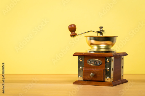 Fotografie, Obraz  Vintage manual coffee grinder on wooden table with color wall background
