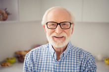 Close Up Portrait Grey Haired He His Him Grandpa Sincerely Gladly Toothy Smiling Wearing Specs Casual Checkered Plaid Shirt Jeans Denim Outfit Standing Bright Light Flat Kitchen Room