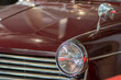 Vintage burgundy classic car. Close-up of headlamp and grill.