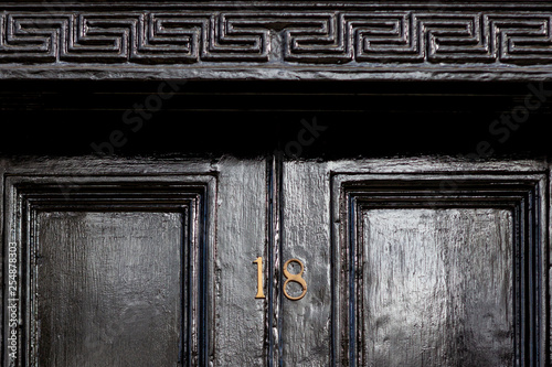 Photographie  House number 18 in bronze on a black wooden entrance door with the eighteen in b