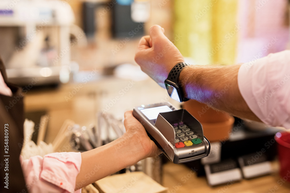 Fototapeta Person paying at cafe with smart watch wirelessly on POS terminal