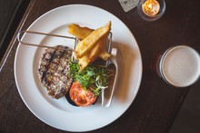 Grilled Steak And Chips On Pub Table