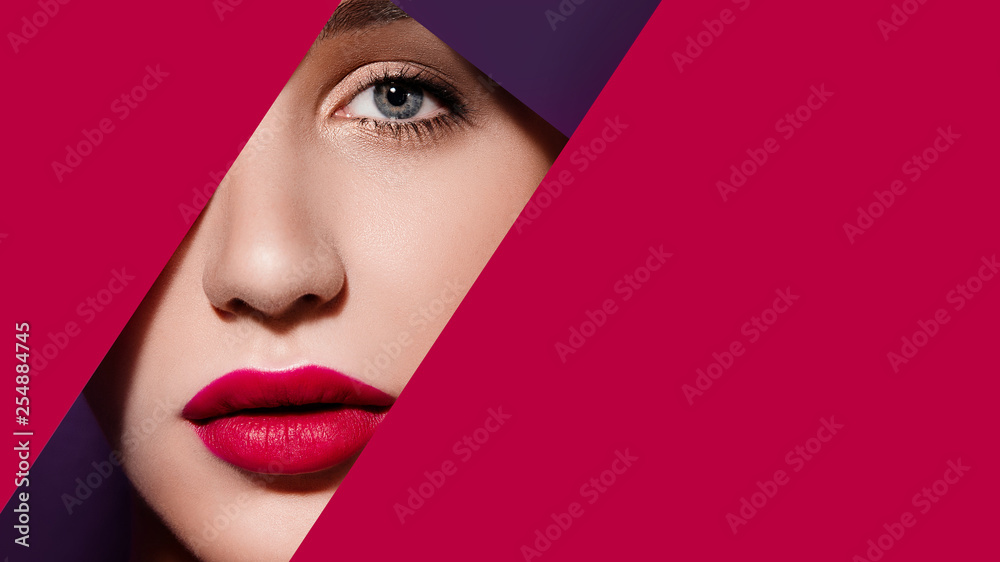 Fototapeta Plump bright red lips in red and violet paper frame. Young model face. Close up beauty photo. Geometry and minimalism. Creative fashion makeup, beautiful woman, clear skin