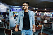Stylish asian man wear on jeans jacket and glasses posed against table on club.