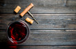 glass of red wine with a corkscrew and corks.