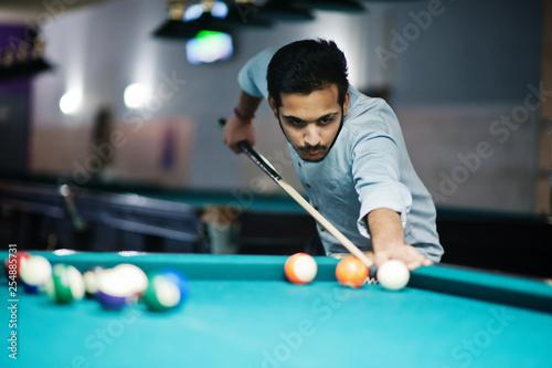 Canvastavla Stylish arabian man wear on jeans playing pool billiard on bar.