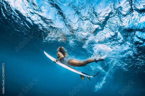 Carta da parati Surfer woman dive underwater. Surfgirl dive under big wave