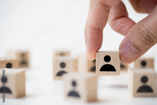 Fotografie, Obraz  Hand of a businessman picking a wooden cube block with icon people standing out from the crowd