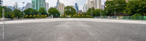 Aluminium Prints Dark grey Empty asphalt road with city in the background