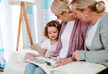 A Small Girl With Mother And Grandmother At Home, Looking At Photographs.