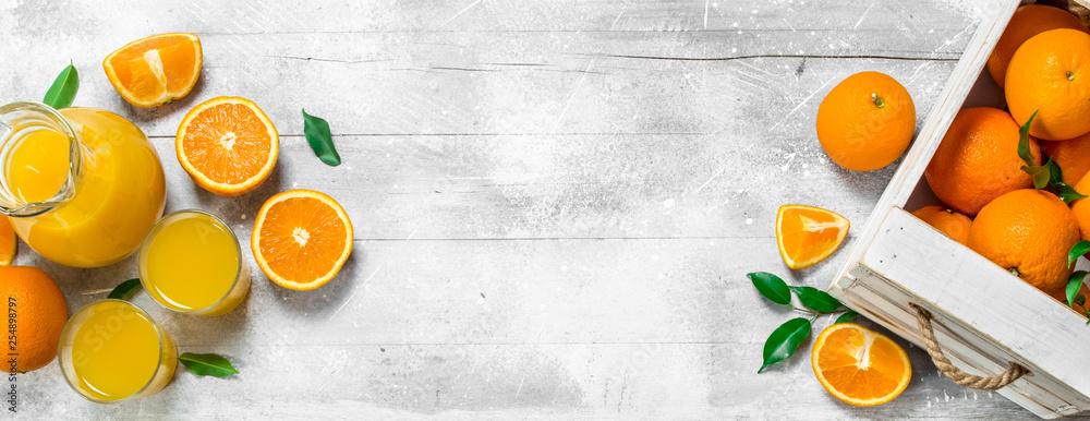 Fototapeta Orange juice in glass pitcher and fresh oranges.