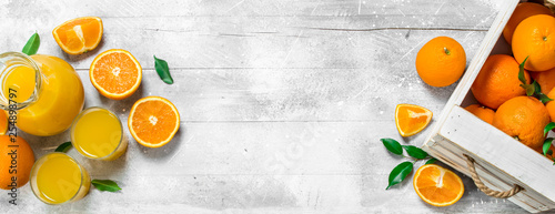 Fotografia Orange juice in glass pitcher and fresh oranges.