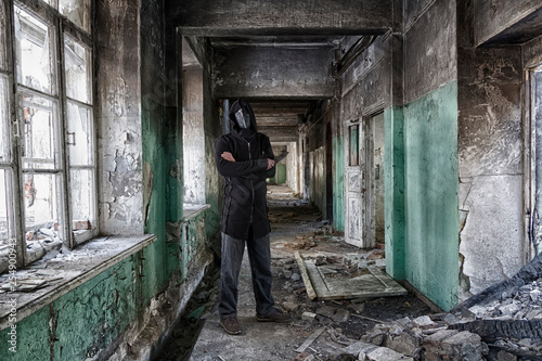Aluminium Prints Africa Danger maniac with knife in hand, in leather mask of lague doctor and hood, inside old abandoned house