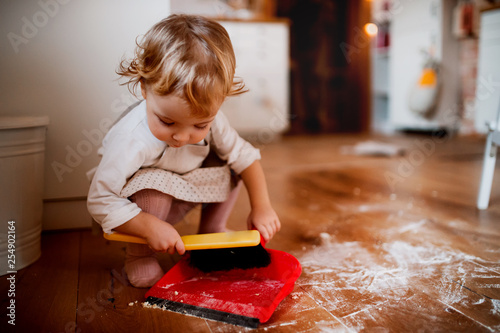 Fotografía  A small toddler girl with brush and dustpan sweeping floor in the kitchen at home