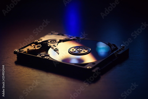 Stampa su Tela  Open / disassembled hard drive on the table in dark colors and lighting close-up