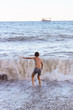 The boy frolics in the big waves