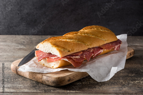Spanish serrano ham sandwich on wooden table.
