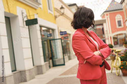 Fotografija  A dark-haired woman in fashionable clothes of the color of the year 2019 living coral standing in the shopping mall