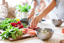 Woman Is Cooking In Home Kitchen. Female Hands Cut Salami, Vegetables, Greens, Tomatoes On Table On Wooden Boards. Ingredients For Preparing Italian Or French Food. Lifestyle Moment.
