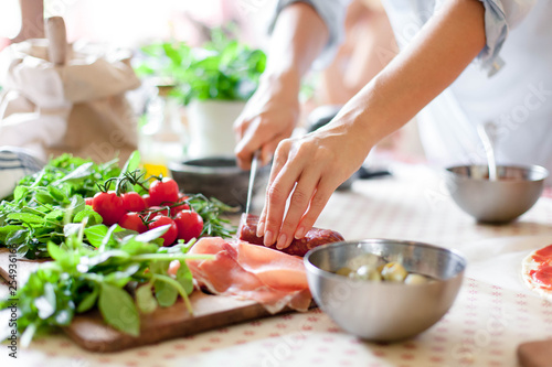 Fototapeta Woman is cooking in home kitchen. Female hands cut salami, vegetables, greens, tomatoes on table on wooden boards. Ingredients for preparing italian or french food. Lifestyle moment. obraz