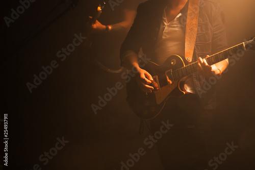 Obraz na plátně Guitarist on a dark stage