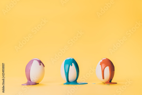 Fotografía  color paint flowing on three egg at yellow background