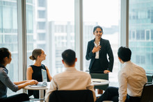 An Asian Indian Businesswoman Is Ingeniously Explaining With Her Diverse Team In A Conference Room. She's Wearing A Black Blazer And White Blouse With A Black Skirt.
