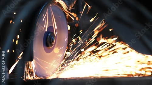 Fotografie, Obraz  Close-up of worker at construction plant saws metal using circular saw