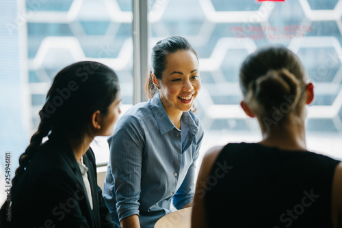 Fototapety, obrazy: Image of a young Asian Chinese woman manager in their office chatting with her team. She is smiling as she listens to her colleague discussing something about their new project.