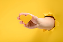 Hand Giving A Yellow Heart