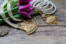 Indian Decorations For Dancing Kathak: Bracelets, Necklace. Purple Ultraviolet Tulips On Old Rustic Wooden Background. Mothers, Womens Day And Greeting Concept