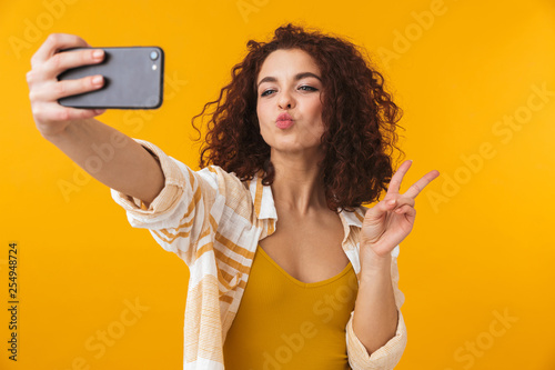 Fototapeta Image of positive woman 20s with curly hair smiling and taking selfie photo on smartphone obraz na płótnie