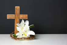 Wooden Cross, Crown Of Thorns And Blossom Lilies On Table Against Color Background, Space For Text