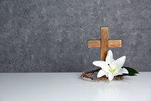 Wooden Cross, Crown Of Thorns And Blossom Lily On Table Against Color Background, Space For Text