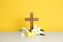 Wooden Cross, Easter Eggs And Blossom Lilies On Table Against Color Background