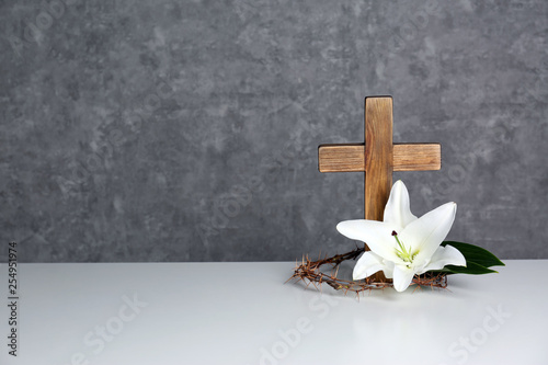 Fotografie, Obraz Wooden cross, crown of thorns and blossom lily on table against color background