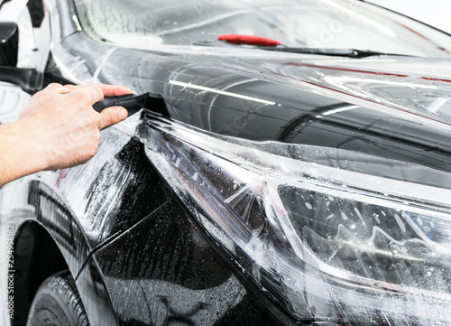 Car wrapping specialist putting vinyl foil or film on car Wallpaper Mural