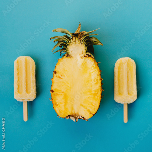 Fotografiet  Tropical flat lay of three vegan popsicle and half of ripe pineapple on cyan bac