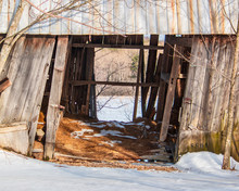Abandoned Decaying Barn With Rusty Metal Roof In Winter Beginning To Collapse