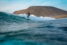 Surfer Riding Waves On The Island Of Fuerteventura In The Atlantic Ocean