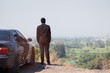 African Businessman standing on top of rock cliff with car