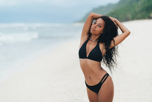 Sexy African American Girl In Swimwear Resting On Ocean Beach. Young Black Skinned Woman With Curly Hair Stands On Seashore