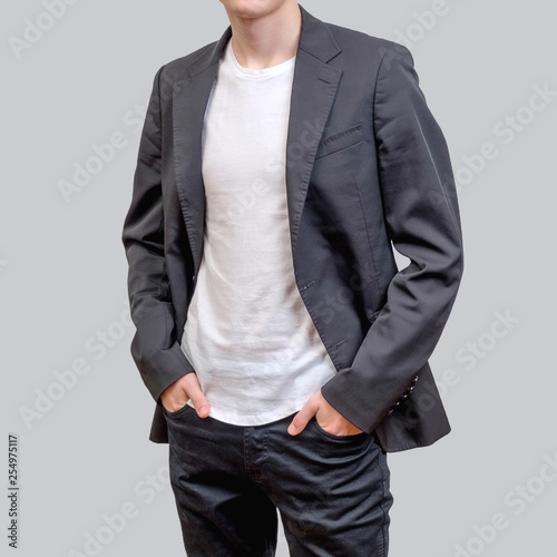 Photo Trendy young man wearing grey blazer and dark jeans, standing against a grey background