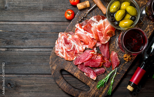 Antipasto background. Different meat snacks with red wine. - 254977182