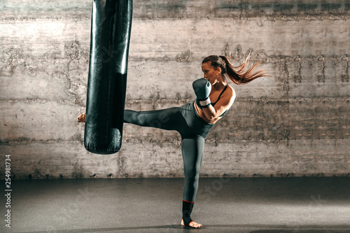 Dedicated strong brunette with ponytail, in sportswear, bare foot and with boxing gloves kicking sack in gym фототапет