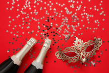 Two Champagne Bottles, Carnival Mask And Confetti Stars On Red Background. Christmas Background, Top View, Copy Space
