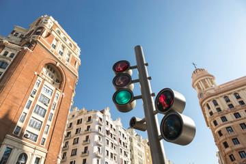 Semáforo en verde y con reflejos de edificio singular del centro de Madrid, con edificios al fondo