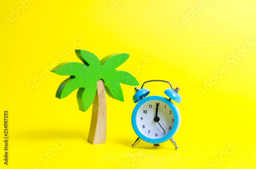 Leinwand Poster  Palm tree and blue alarm clock on a yellow background