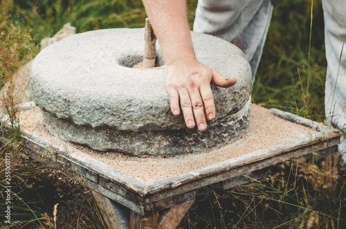 Photo  The ancient quern stone hand mill with grain